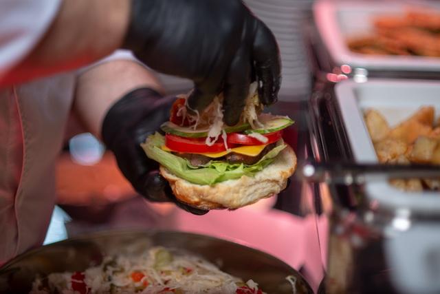 Összeáll egy tökéletes hamburger: édeskés buci, érlelt húsból gyúrt szaftos húspogácsa, zöldésgekből és mártásokból álló körítés